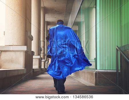 A business man is dressed as a super hero with a blue cape running in the city for a urgent job or leadership concept.