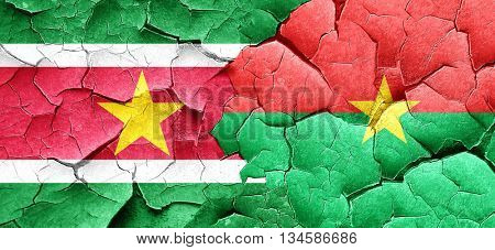 Suriname flag with Burkina Faso flag on a grunge cracked wall