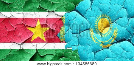 Suriname flag with Kazakhstan flag on a grunge cracked wall