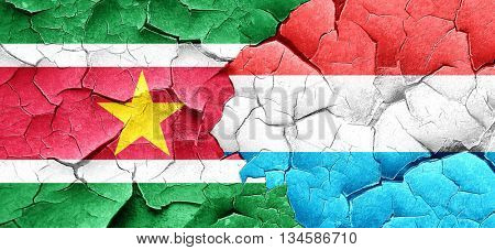 Suriname flag with Luxembourg flag on a grunge cracked wall