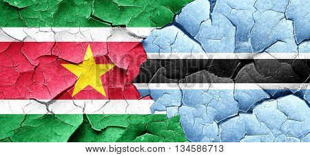 Suriname flag with Botswana flag on a grunge cracked wall