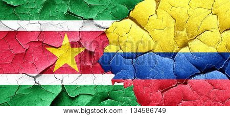 Suriname flag with Colombia flag on a grunge cracked wall