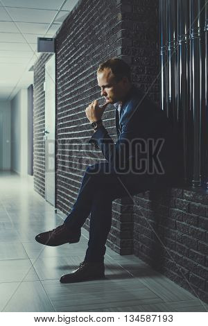 European Businessman Is Sitting In The Corridor Of Office And Thinks.