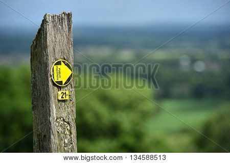 Footpath sign with typical English countryside in background