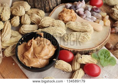 Peanut butter and peanut on wood background