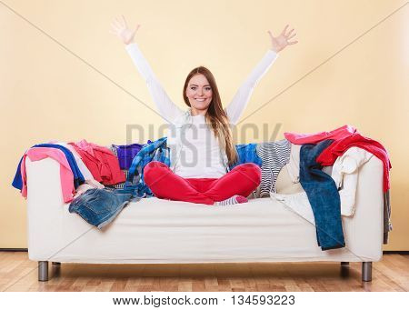 Happy Woman Sitting On Sofa In Messy Room At Home.