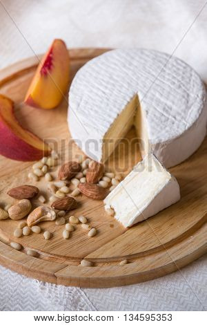 White delicious homemade camambert cheese on a wooden plate served with almonds cashew pine nuts and peach. Dessert for a family dinner. Brie.