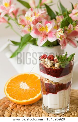 Homemade parfait serverd in high glasses with yogurt and organic raspberries nuts and mint. Delicious snack for healthy life. Breakfast on a straw tablemat with spoons and flowers and half of orange