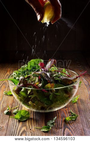 Fresh lemon burst. Hand squeeze a lemon on salad with mixed greens (arugula, chard) on wooden rustic wooden tabletop. Organic food in low key