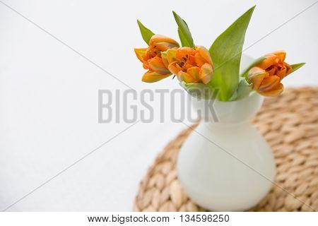 Three fresh spring orange tulips in a nice white glass vase on the straw board. Home decor for spring and Easter. Bunch of flowers
