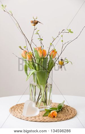 Fresh spring bunch of orange tulips and green leaves and two small birds in a nice cristal glass vase and a cute heart symbol on the straw board and table with a tablecloth. Home decor for spring and Easter. Beautiful flowers.