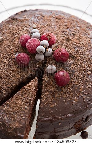 Homemade fresh chocolate birthday cake with organic frozen berries and chips on the top. Piece of cake and celebration.