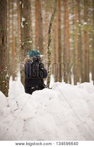 8 years old boy building a snow castle and playing with snowballs in the forest.