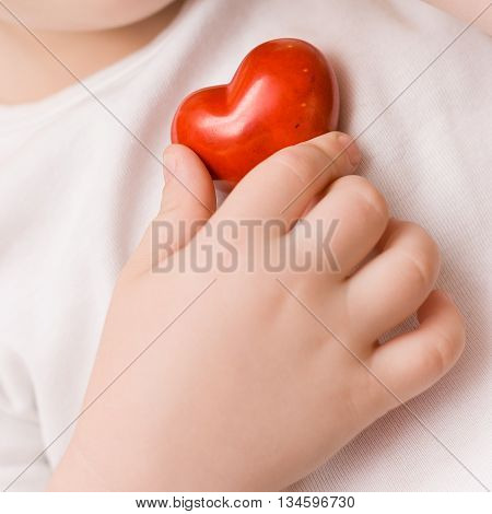 A small red heart in hand of child. Love. Happiness. Care. Healthcare. Childhood.