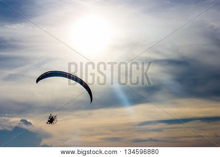 Silhouette man flying with paramotor in the blue sky background