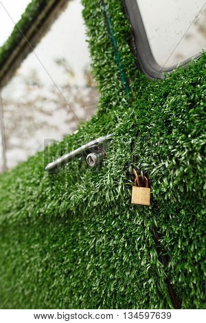 A gold lock on an old green grass decorated car. Funny and ecological design idea for a car decoration. New generation of future cars.