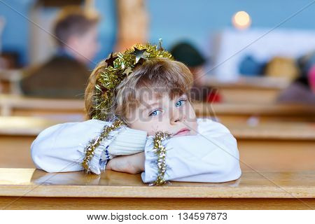 Beautiful little kid boy as an angel in Christmas story in a church. Happy adorable blond child with lights and xmas tree on background.