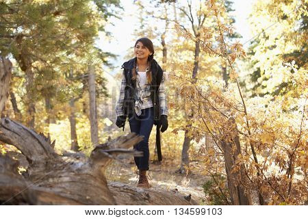 Hispanic girl walking along a fallen tree in a forest