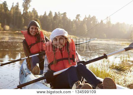 Mother and daughter kayaking on rural lake, close up