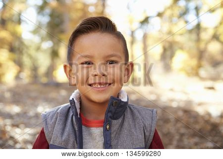 Head and shoulders portrait of a Hispanic boy in a forest