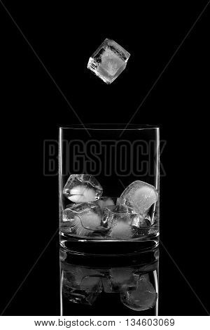 Ice cube falling into a glass on a black background