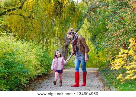 beautiful young mother and her little daughter in beautiful autumn forest. Cute kid girl and woman walking together. Family portrait, fall season.