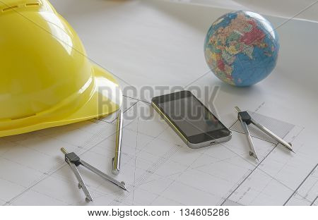Engineer work concept background with world model, helmet, pen and mobile phone.