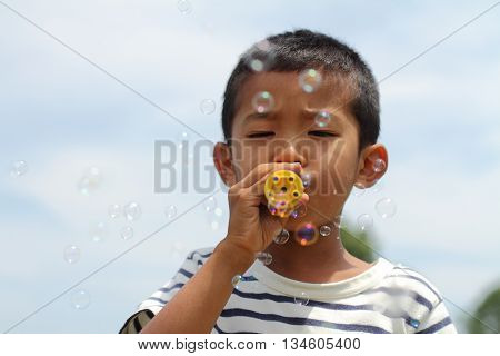 Japanese boy playing with bubble (first grade at elementary school)