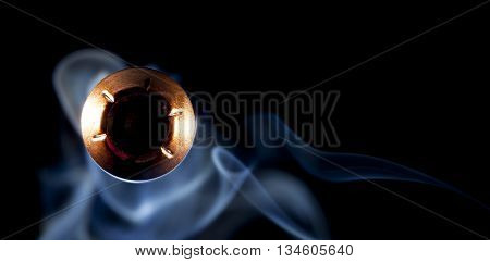 Hollow point bullet with a copper jacket and smoke coming at the camera