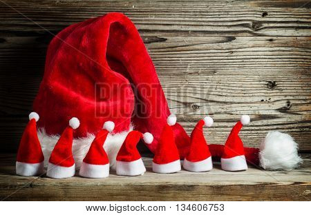 small and large Christmas hats on old wooden table