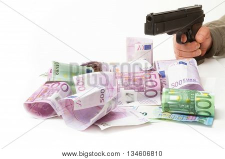 Money and gun in hand on a white background
