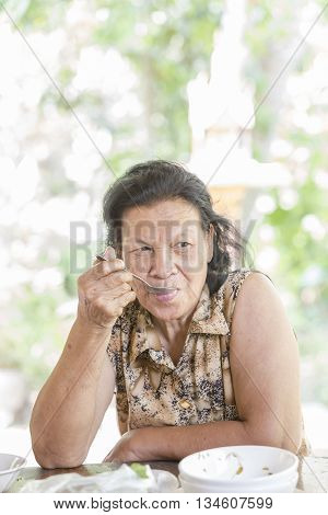 Portrait of happy beautiful senior woman eating her lunch/dinner at the table of home