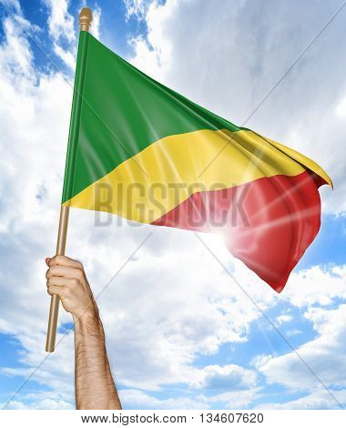 Person's hand holding the Congo Republic national flag and waving it in the sky, part 3D rendering
