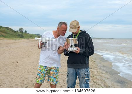 Two men with a drone and controller in hands are discussing characteristics of flight and video of drone while they are on the beach. Cloudy summer day on the seaside.
