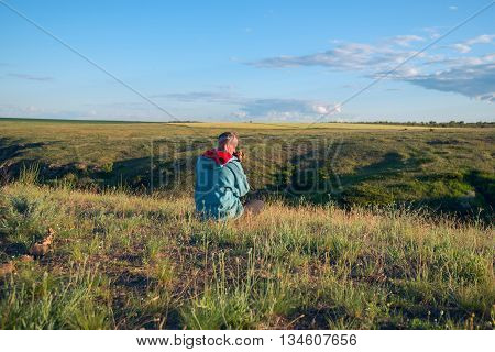 Man with a dog sitting in prairie during sunset.