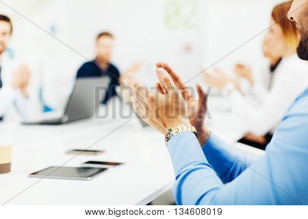 Selective focus of business people clapping hands at meeting