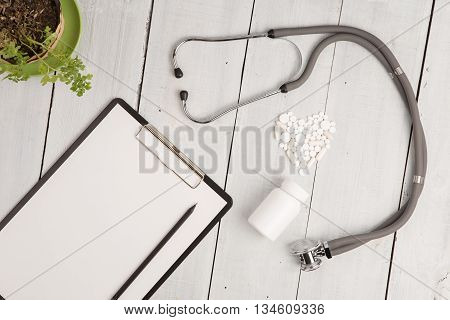 Medical Concept - Stethoscope, Pad, Bottle And White Heart Of Pills And Capsules