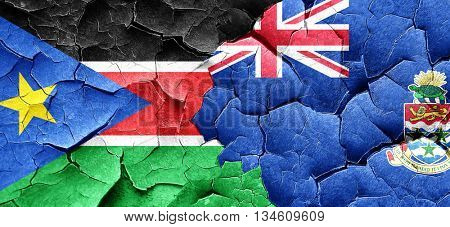 south sudan flag with Cayman islands flag on a grunge cracked wa