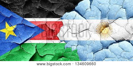 south sudan flag with Argentine flag on a grunge cracked wall