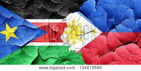south sudan flag with Philippines flag on a grunge cracked wall