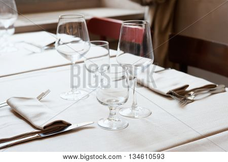 Wine glasses and silverware on restaurant table