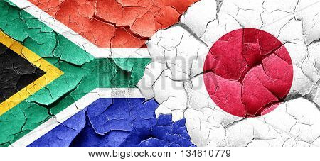 South africa flag with Japan flag on a grunge cracked wall
