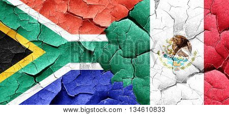 South africa flag with Mexico flag on a grunge cracked wall