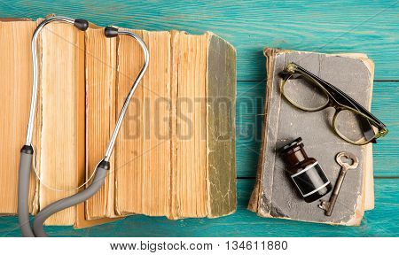 Old medical books with stethoscope glasses bottle and key on blue wooden background