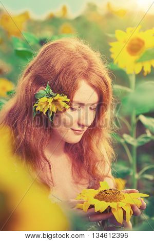 Beautiful red-haired woman with sunflowers Girl in the field with sunflowers. Young model on the background of summer  landscape. Summer warm sunny scene