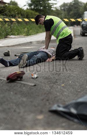 Policeman Resuscitating Injured Man