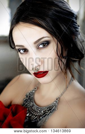 Beautiful woman with cute face bright make up red lips and piercing on nose