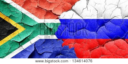 South africa flag with Russia flag on a grunge cracked wall