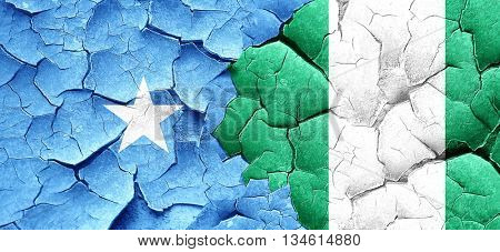 Somalia flag with Nigeria flag on a grunge cracked wall
