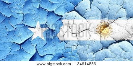 Somalia flag with Argentine flag on a grunge cracked wall